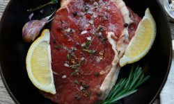 Raw beef steak closeup background with spices and herbs.